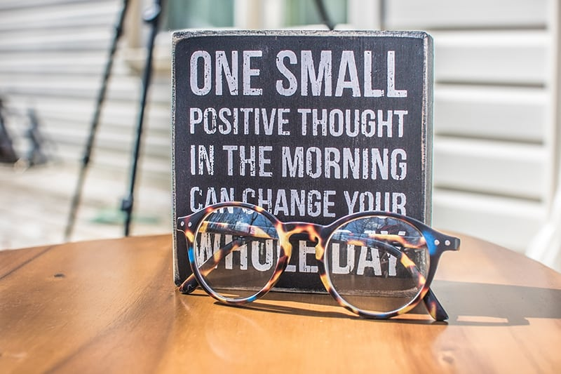 ein Foto mit einem Zitat und Brillen auf dem Tisch