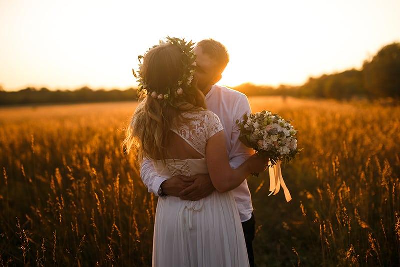 ein Hochzeitspaar, das sich küsst, während es während des Sonnenuntergangs auf dem Feld steht