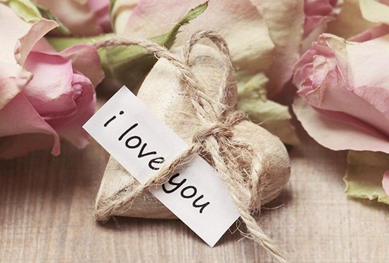 ein Kieselstein in Form des Herzens mit I Love You Note