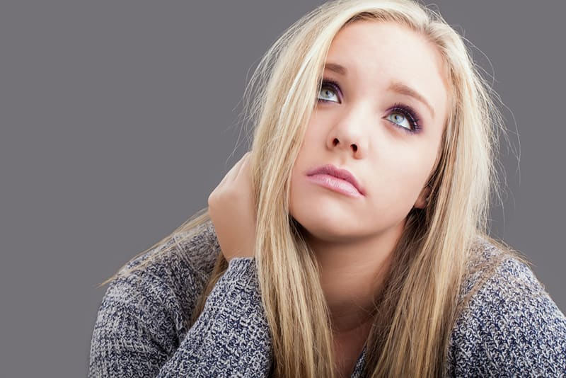 a girl with blond hair looking up and feeling hopeless