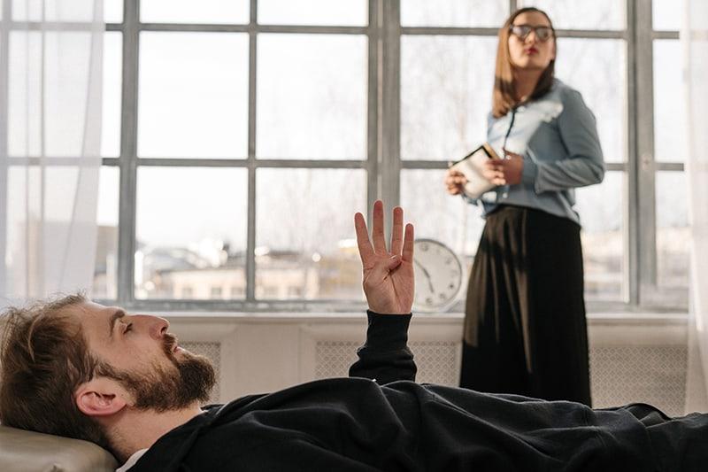 Ein Mann, der auf dem Sofa liegt, während der Therapeut am Fenster steht