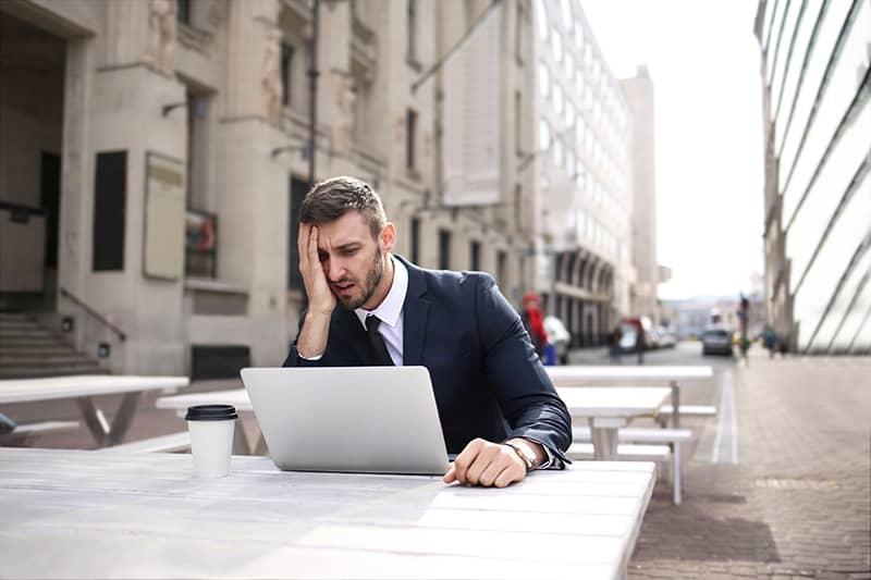 Ein Mann berührt das Gesicht mit der Handfläche, während er am Laptop arbeitet, und kann sich nicht auf die Arbeit konzentrieren