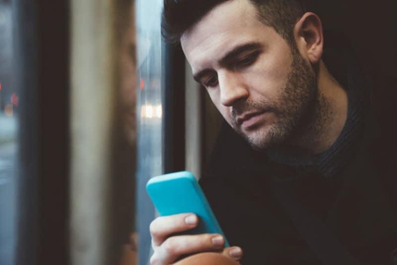 ein Mann, der auf einem Handy tippt(1)