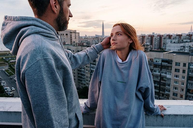Ein Mann, der die Haare seiner Freundin berührt, während er sich ansieht