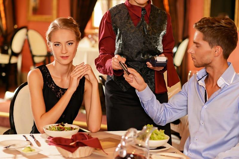 Ein Mann, der eine Rechnung mit einer Kreditkarte bezahlt, während er mit einer Freundin im Restaurant sitzt