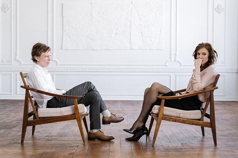 ein Mann, der eine nachdenkliche Frau ansieht, die ihm gegenüber im Sessel sitzt