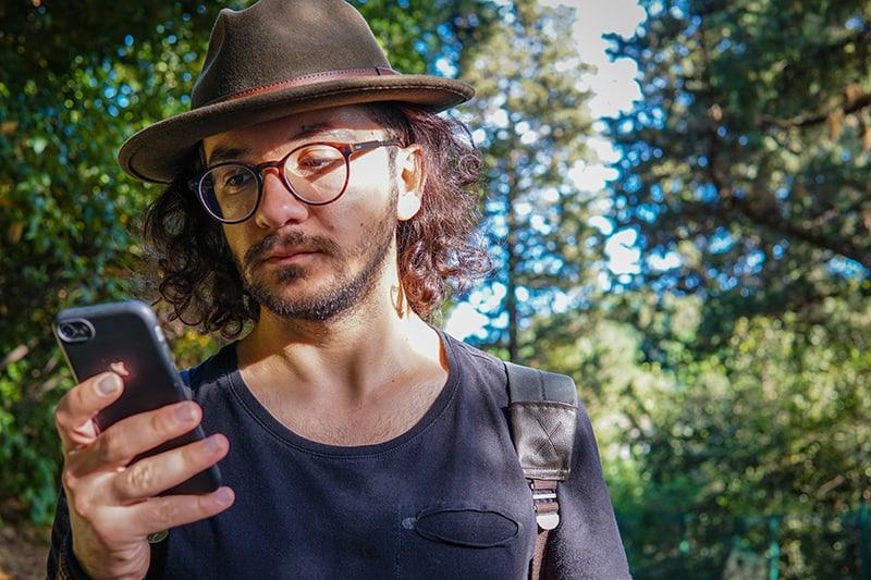 ein Mann, der einen Hut trägt, der ein Smartphone beim Gehen im Park betrachtet