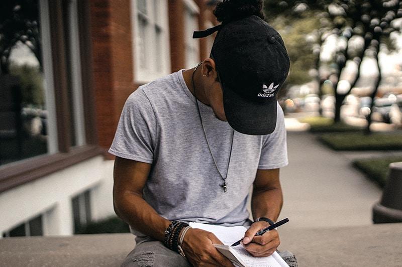 ein Mann, der einen Liebesbrief schreibt, während er auf der Betonwand sitzt