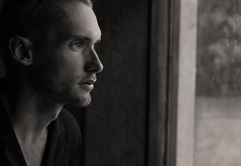 Ein Mann, der sich nostalgisch fühlt und durch das Fenster schaut