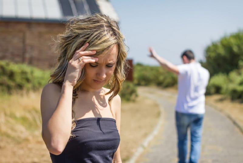 ein Mann, der von einer traurigen Frau geht, die auf der Straße steht