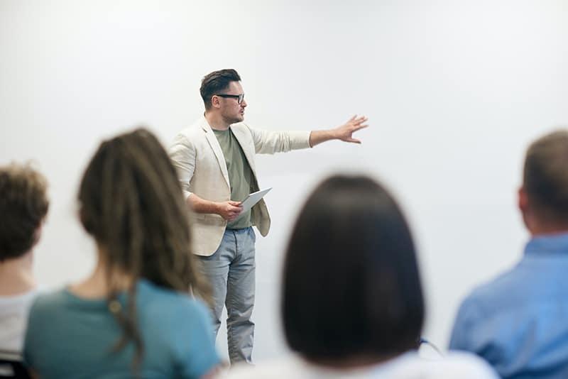 Ein Mann steht vor einer Gruppe von Menschen, die einen Vortrag halten