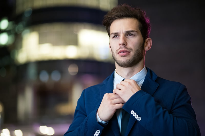 ein Mann im blauen Anzug, der Krawatte bindet