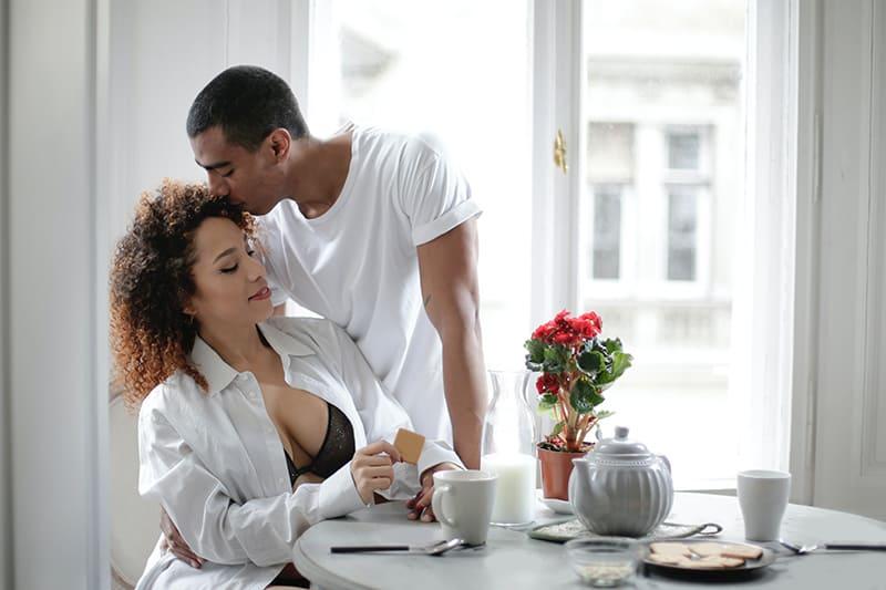 Ein Mann küsst die Stirn seiner Freundin, während er zu Hause zusammen frühstückt