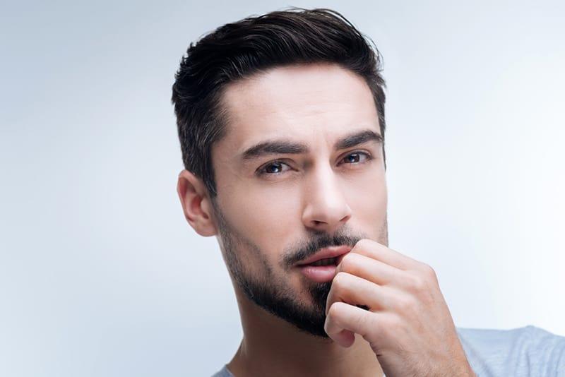 Ein Mann mit Bart berührt seine Lippen mit der Hand