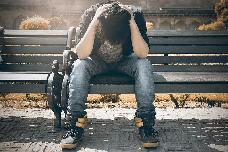 Ein Mann sitzt auf der Bank und hält den Kopf, während er nach unten schaut