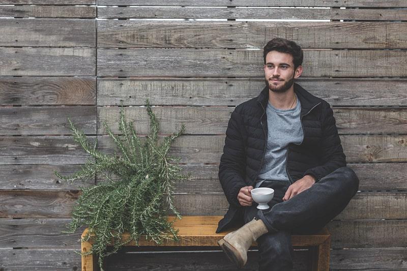 Ein Mann sitzt auf der Bank und hält eine Tasse Tee