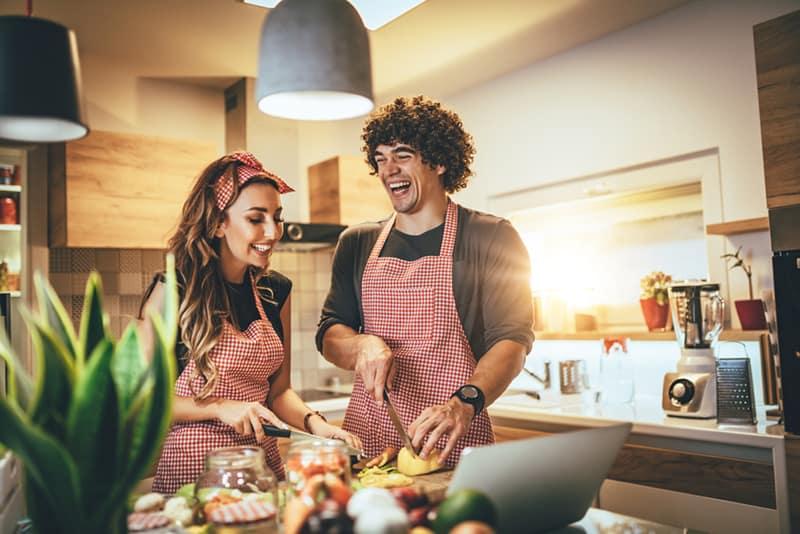 Ein Mann und eine Frau bereiten Essen in der Küche zu und lachen