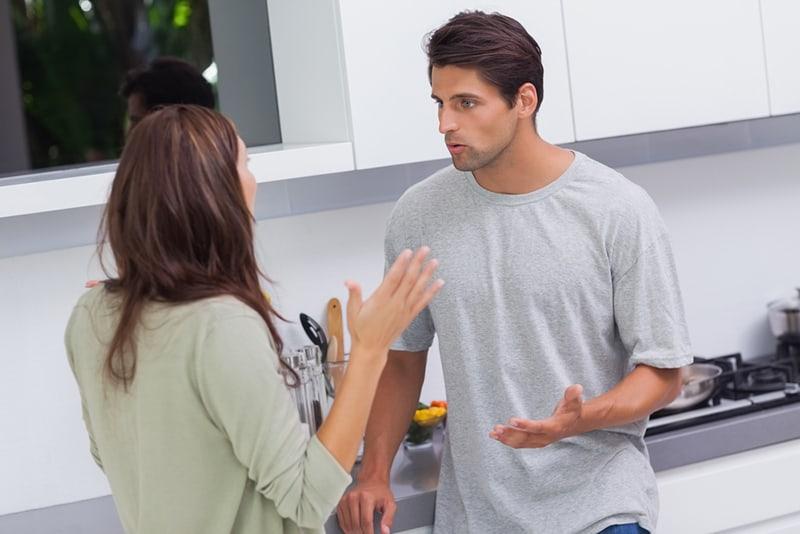 Ein Mann und eine Frau streiten sich, während sie in der Küche stehen