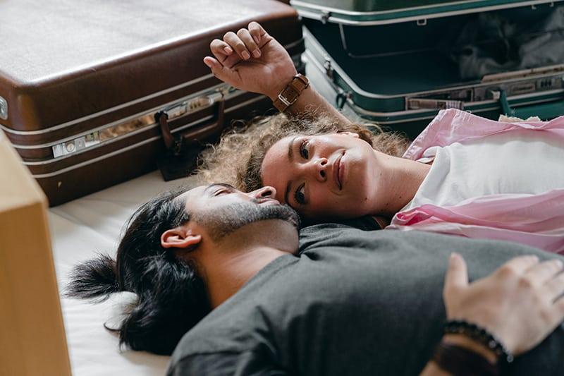 ein Paar, das sich ansieht, während es mit Koffern auf dem Bett liegt