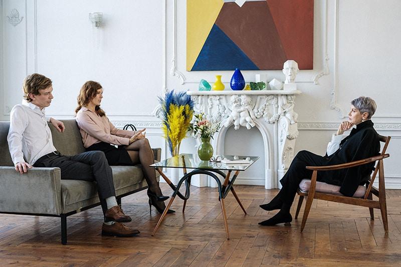 Ein Paar spricht mit einem Therapeuten auf der Couch