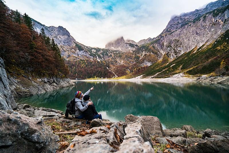 Ein Paar sitzt auf dem Felsen in der Nähe des Sees und beobachtet die Natur
