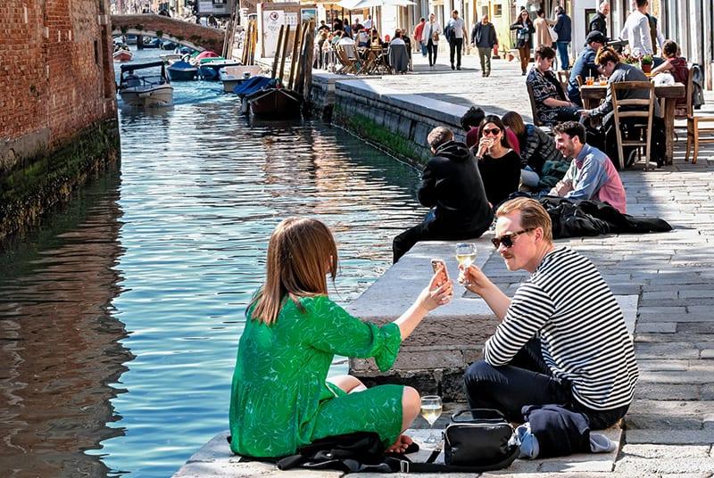 Ein Paar sitzt in der Nähe des Flusses in Venedig und trinkt Wein