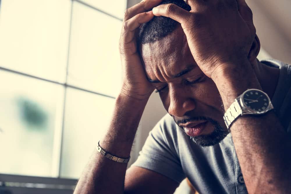 ein Porträt eines depressiven schwarzen Mannes, der seinen Kopf hält
