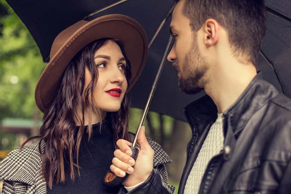ein Porträt eines liebenden Paares unter einem Regenschirm