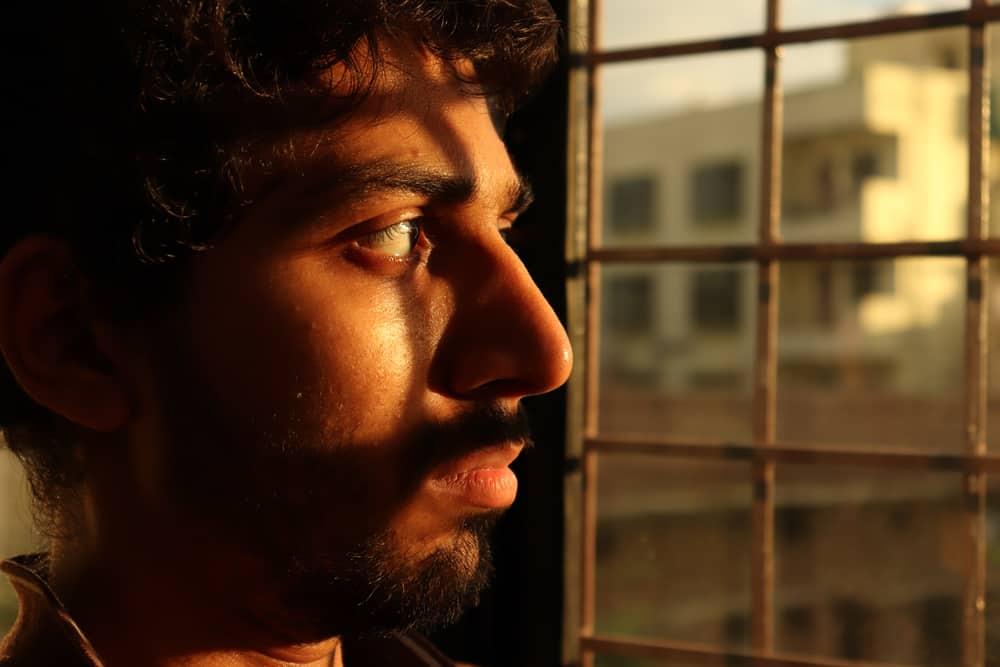 ein Porträt eines traurigen Mannes, der aus dem Fenster schaut