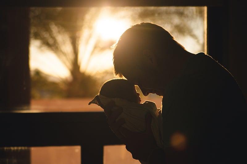 ein Vater, der ein Baby auf der Terrasse während des Sonnenuntergangs hält