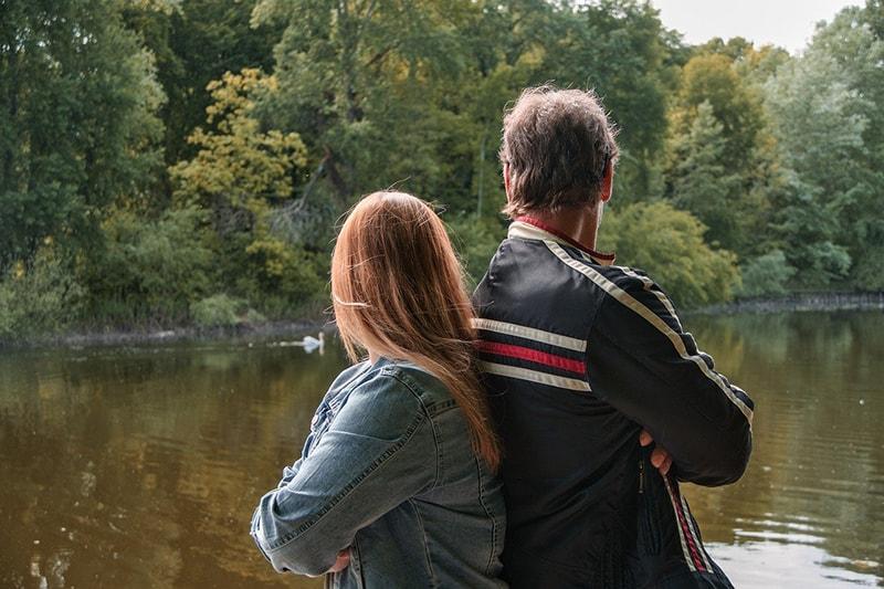 Ein Vater und eine Tochter lehnen sich aneinander, während sie in der Natur rumhängen