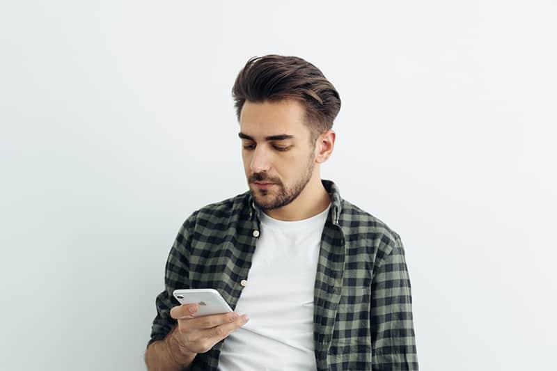 ein bärtiger Mann, der ein Smartphone betrachtet, während er nahe einer weißen Wand steht