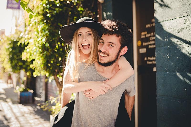 Ein glücklicher Mann, der seine lächelnde Freundin auf dem Rücken trägt, während er auf dem Bürgersteig geht