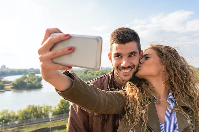 Ein glückliches Paar macht ein Selfie mit einem Smartphone, während es im Park steht