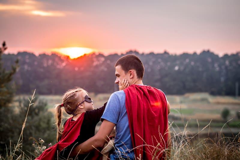 ein kleines Mädchen, das das Gesicht ihres Vaters berührt, während es zusammen auf dem Feld sitzt und beide ein Superheldenkostüm tragen