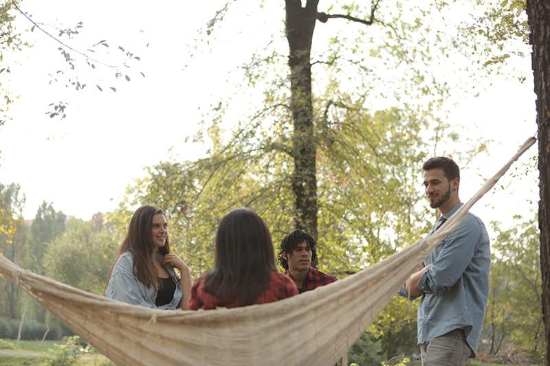 ein lächelnder Mann, der eine Frau betrachtet, die im Hummock sitzt und mit Freunden um sie herum steht