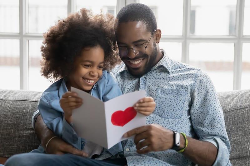 ein lächelnder Vater sitzt mit kleiner Tochter auf der Couch und liest eine Grußkarte