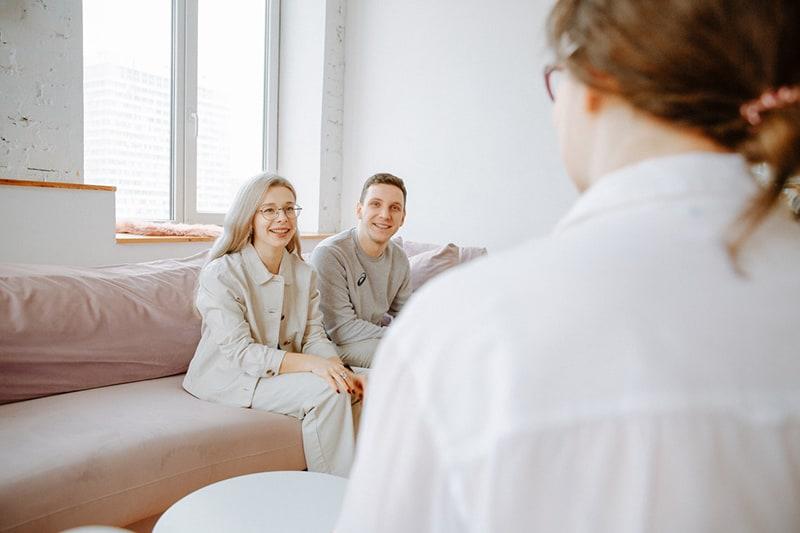 ein lächelndes Paar, das den Eheberater betrachtet, während es auf der Couch sitzt