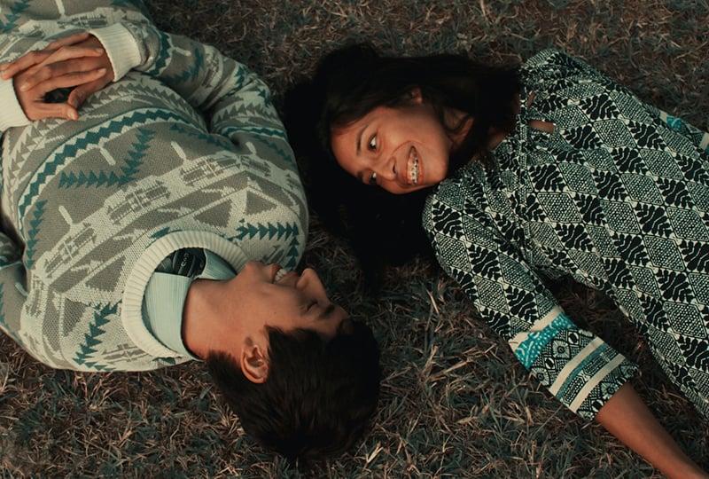 ein lächelndes Paar, das im Gras liegt und sich ansieht