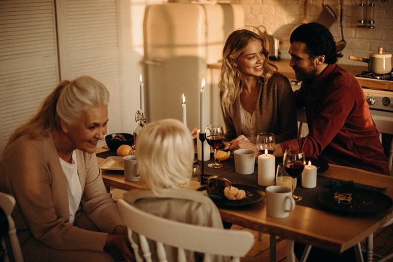 ein lächelndes Paar, das sich ansieht, während es während des Familienessens am Tisch sitzt
