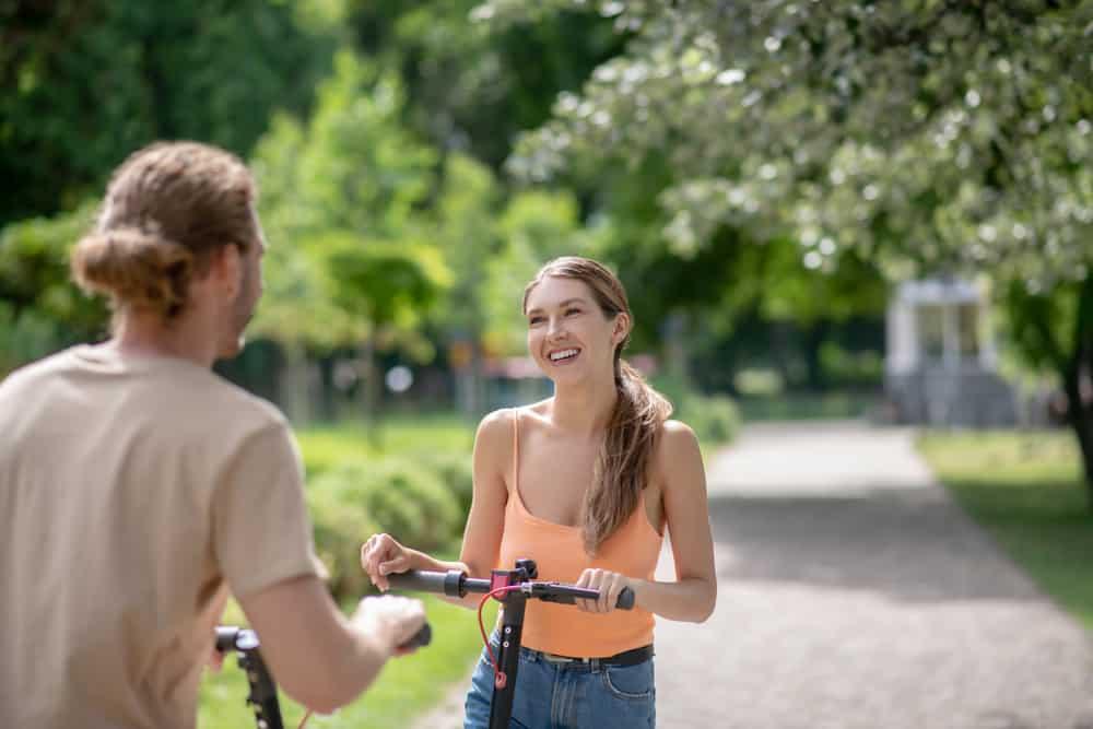 ein lächelndes Paar in einem Park auf Elektrorollern flirten