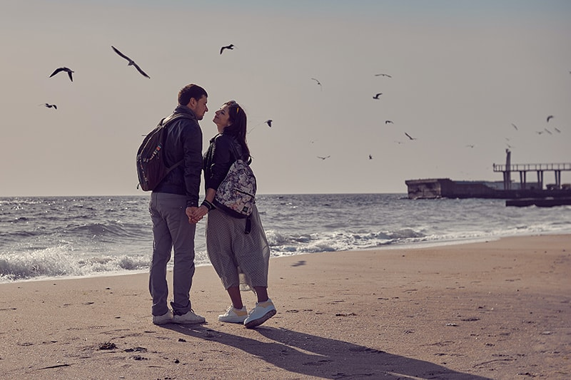 ein liebendes Paar, das Händchen haltend küssen will und an der Küste steht