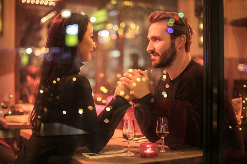 ein liebevolles Paar Händchen haltend im romantischen Restaurant bei einem Date