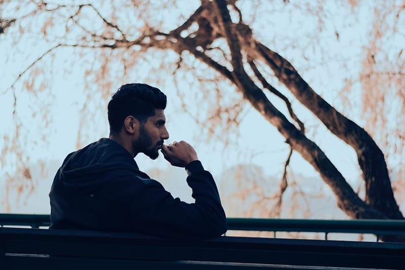 Ein nachdenklicher Mann sitzt alleine auf der Bank und berührt sein Kinn mit der Hand