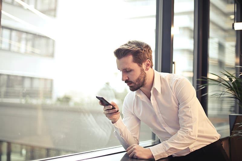Ein nachdenklicher Mann hält sein Smartphone und lehnt sich an das Fenster