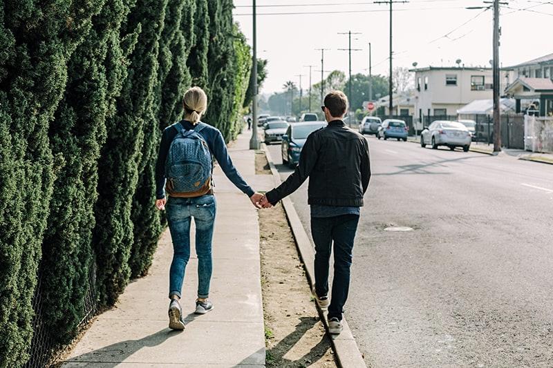 ein Paar Händchen haltend beim Gehen auf dem Bürgersteig