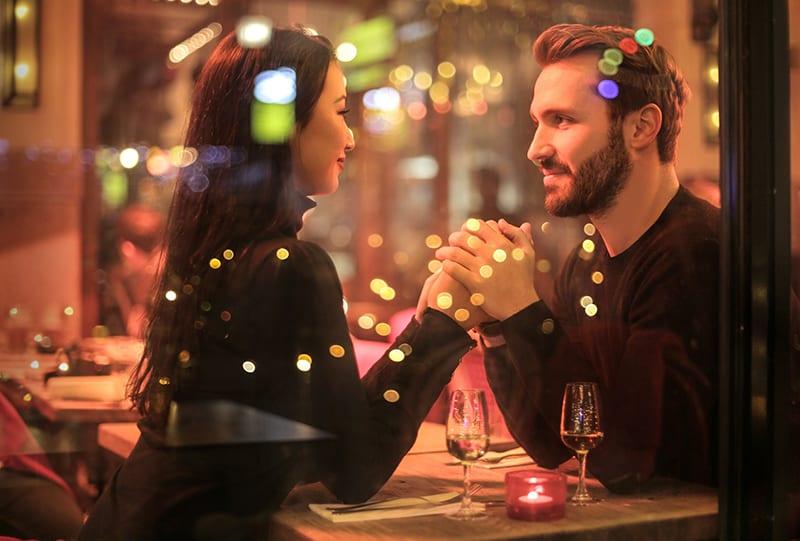Ein Paar, das sich an den Händen hält und sich im romantischen Restaurant ansieht