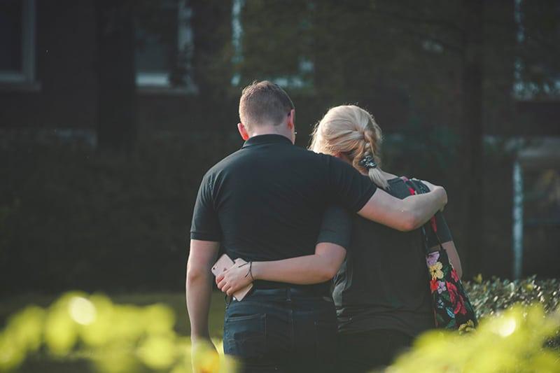 Ein Paar geht im Park spazieren und umarmt sich