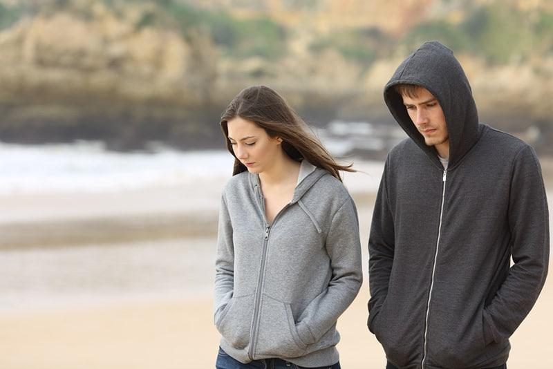 ein trauriges Paar, das zusammen am Strand spazieren geht