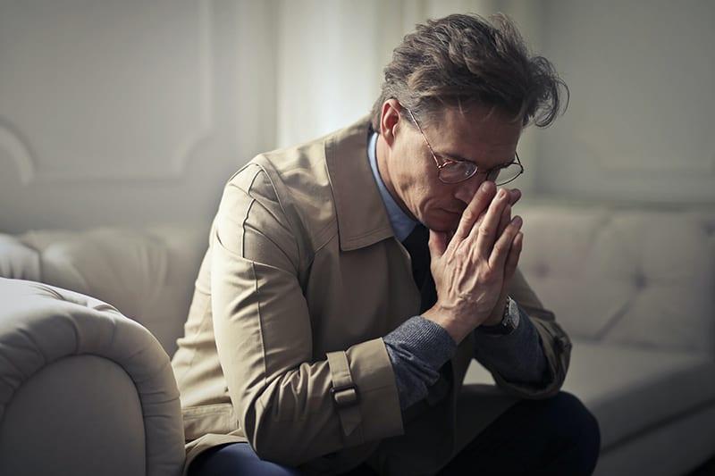 Ein unsicherer Mann sitzt auf der Couch und lehnt den Kopf an seine Handflächen